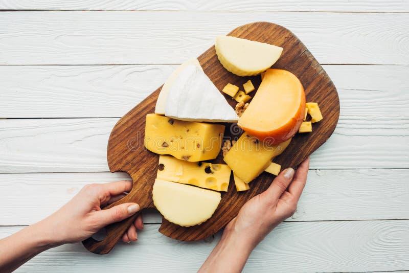 Handen en geassorteerde kaas op houten raad stock afbeelding