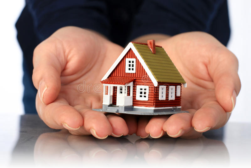 Handen en plattelandshuisje. stock afbeeldingen