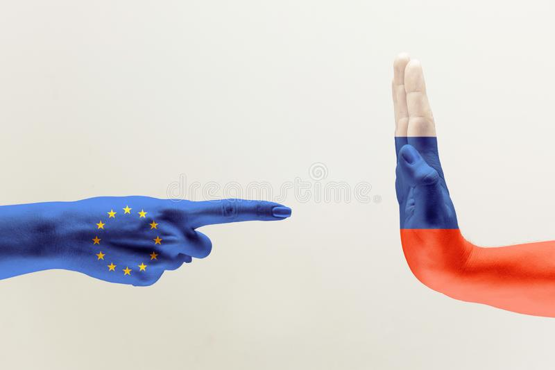 Handen färgade i flaggor av EU och Ryssland arkivbild