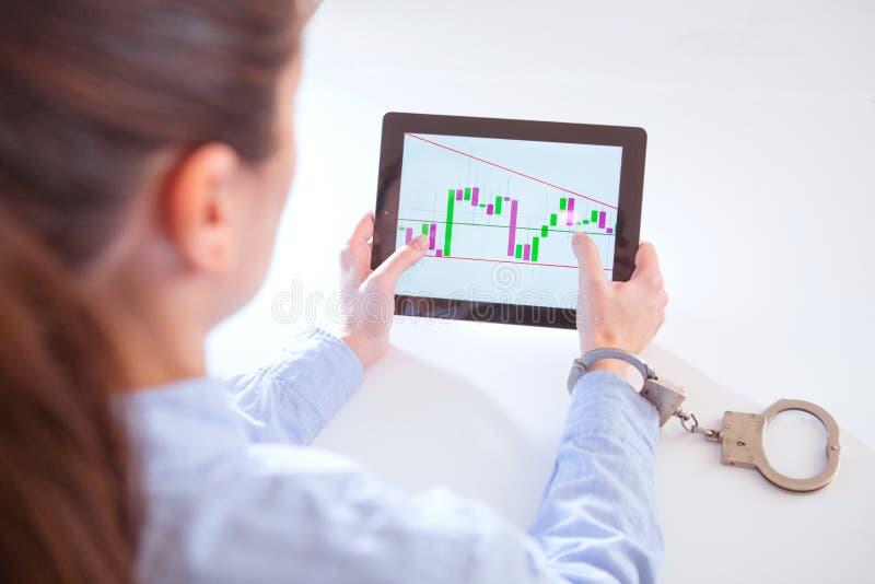 Handen fäste med handbojor och minnestavlan med en finansiell graf på skärmen arkivfoton