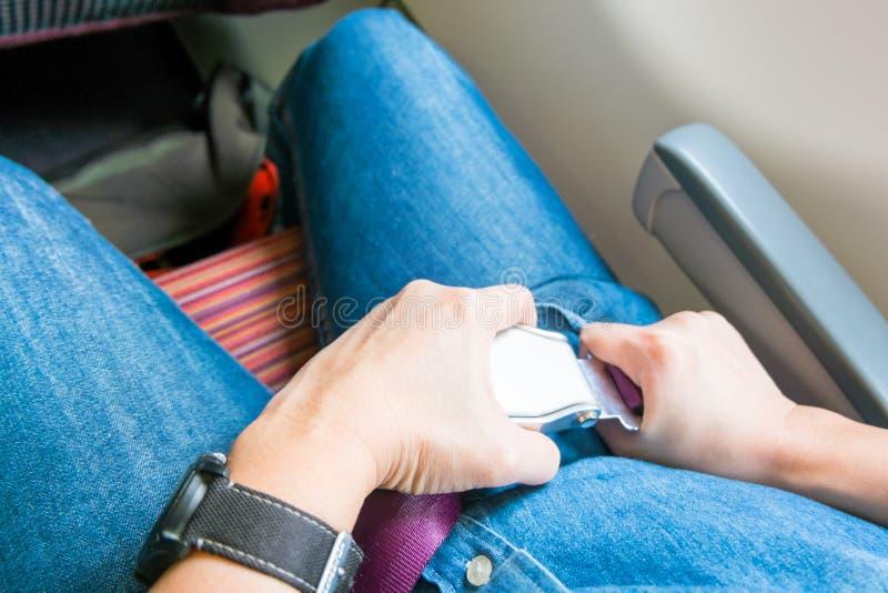 Handen fäster säkerhetsbältet på platsen på flygplanet för tar av arkivbilder