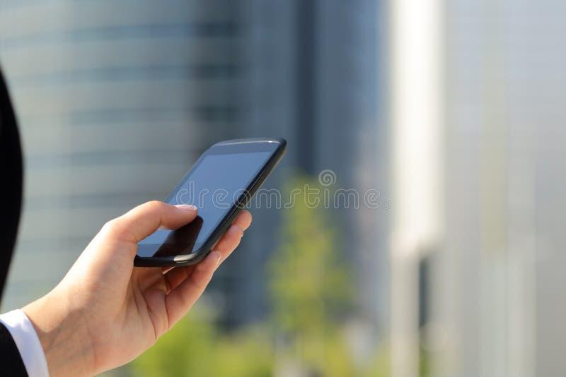 Handen för affärskvinnan som på smsar ilar han, telefonen arkivfoto