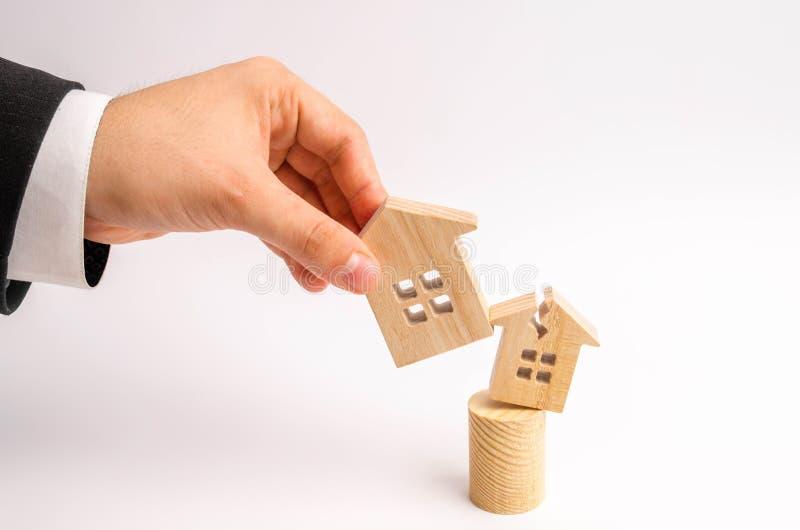 Handen för affärsman` s byter ut det gamla brutna huset med ny begrepp av renovering, renovering av hus och rivning arkivbild