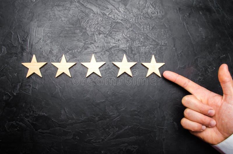 Handen för affärsman` s i dräktpunkterna till den femte stjärnan Få den femte stjärnan Begreppet av värderingen av hotell royaltyfri bild