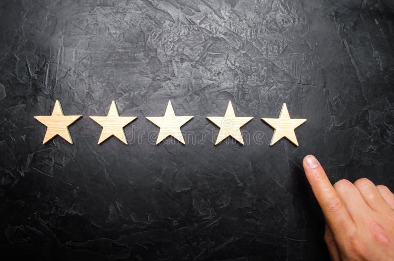 Handen för affärsman` s i dräktpunkterna till den femte stjärnan Få den femte stjärnan Begreppet av värderingen av hotell fotografering för bildbyråer