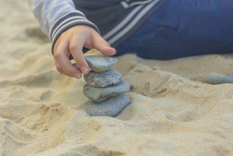 Handen för barn` s bygger ett torn av stenar på gulingen sand1 royaltyfri fotografi