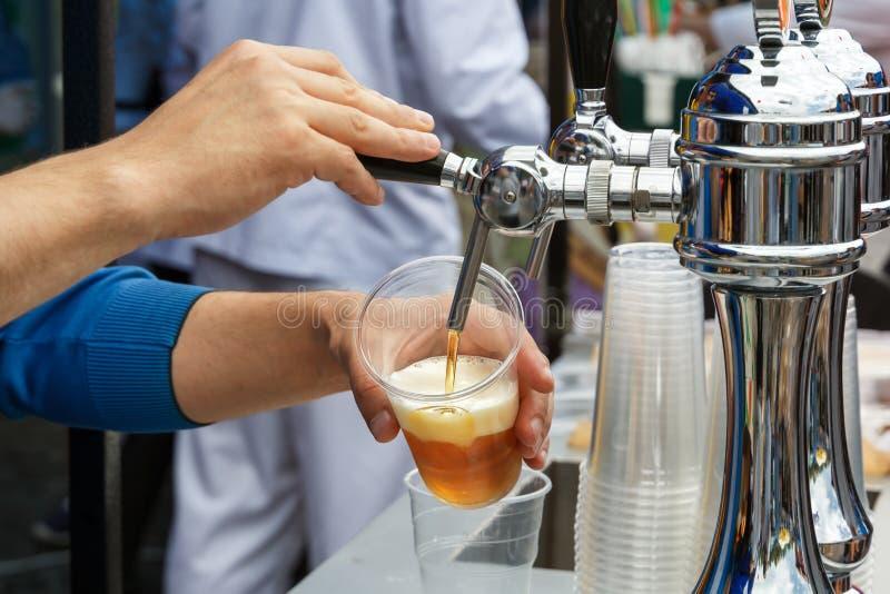 Handen för bartender` s rymmer ett stort exponeringsglas som nytt bärnstensfärgat öl hälls i med skum royaltyfri bild