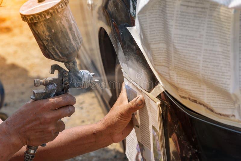 handen för bilrepairmanmålaren med retuschsprutapulverizeren smärtar royaltyfri foto