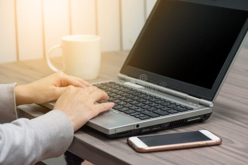 Handen för den unga kvinnan fungerar med datoren arkivfoto