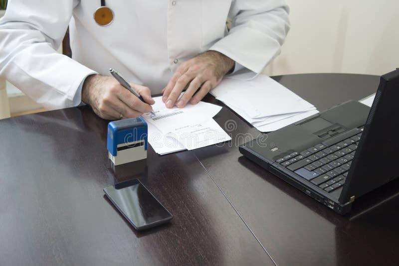 Handen för doktors` s stämplade på receptet Doktorn skriver ett recept på hans skrivbord arkivbilder
