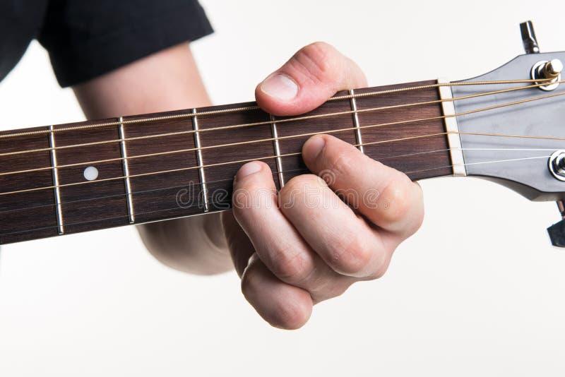 Handen för gitarrist` s klämmer fast ackordet D på gitarren, på en vit bakgrund Horisontal inrama royaltyfria foton