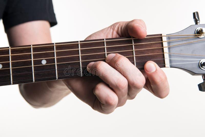 Handen för gitarrist` s klämmer fast ackordet Dmon gitarren, på en vit bakgrund Horisontal inrama royaltyfria foton