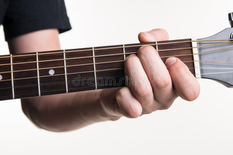 Handen för gitarrist` s klämmer fast ackordet E på gitarren, på en vit bakgrund Horisontal inrama royaltyfri bild