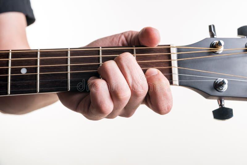 Handen för gitarrist` s klämmer fast ackordet f.m. på gitarren, på en vit bakgrund Horisontal inrama arkivfoto