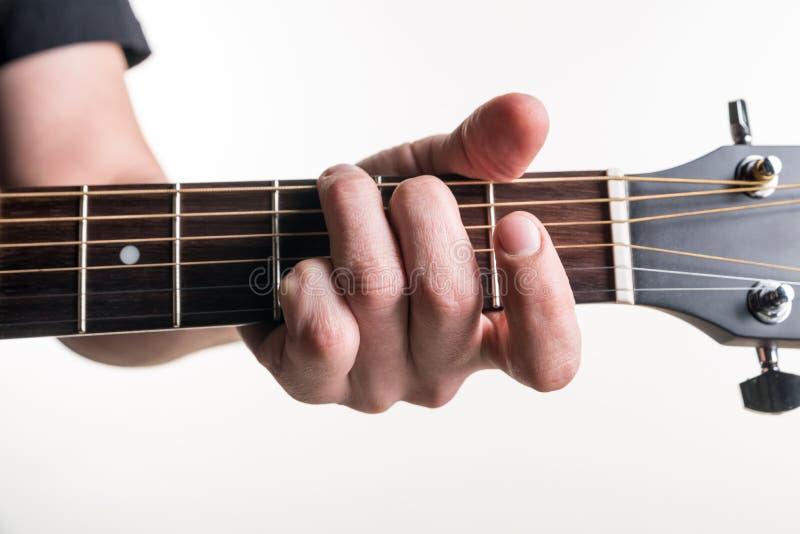 Handen för gitarrist` s klämmer fast ackordGet på gitarren, på en vit bakgrund Horisontal inrama arkivbild