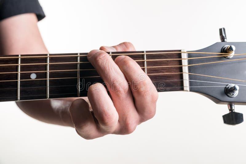 Handen för gitarrist` s klämmer fast ackordGet på gitarren, på en vit bakgrund Horisontal inrama arkivbilder