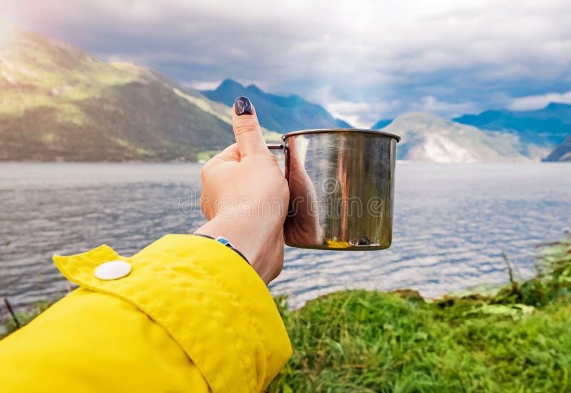 Handen för kvinna` s i gult hänga för lag rånar med varmt te, i att campa nära bergsjön royaltyfria foton