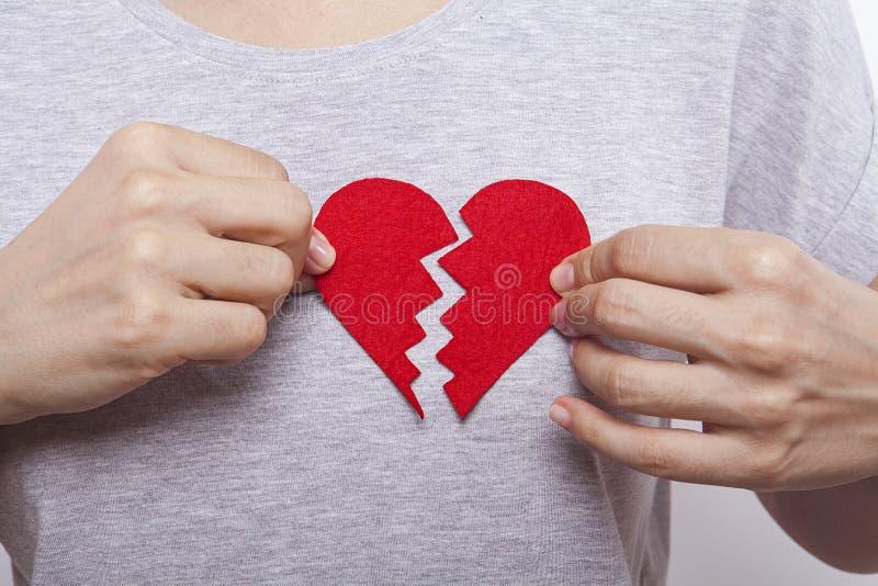 Handen för kvinna` s rymmer bruten röd hjärta royaltyfria bilder