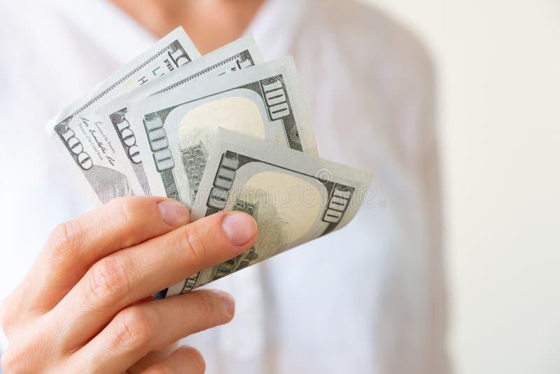 Handen för kvinna` s rymmer två hundratals dollar royaltyfria bilder