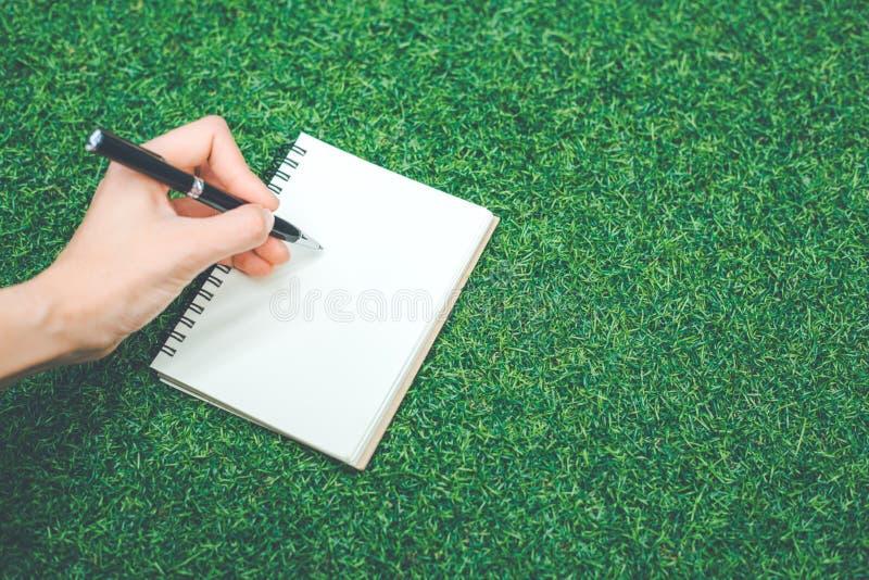 Handen för kvinna` s skriver på en tom notepad med en penna på arkivbilder