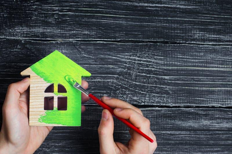 Handen för man` s målar trähuset i den gröna borsten reparation och renovering av huset, miljövänligt hus Energi arkivbild