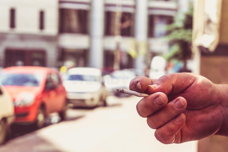 Handen för man` s rymmer en cigarett på en suddig stadsbakgrund som röker i ett offentligt ställe arkivfoto