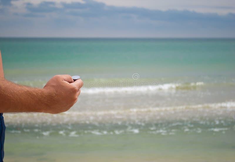 Handen för man` s rymmer ett mynt från metallörnsvansarna mot havet, ska just att kasta ett mynt in i havet för att gå tillbaka arkivfoton