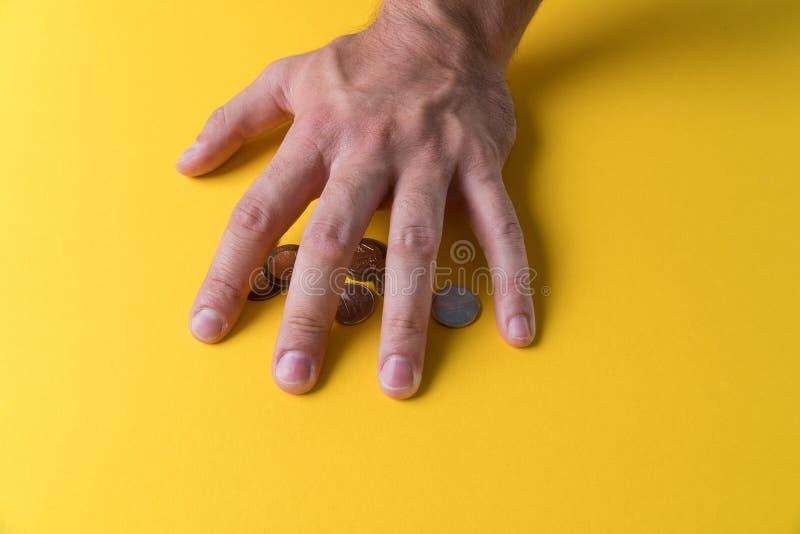 Handen för man` s täckte mynten ditt pengarskydd Brist av pengar royaltyfri fotografi