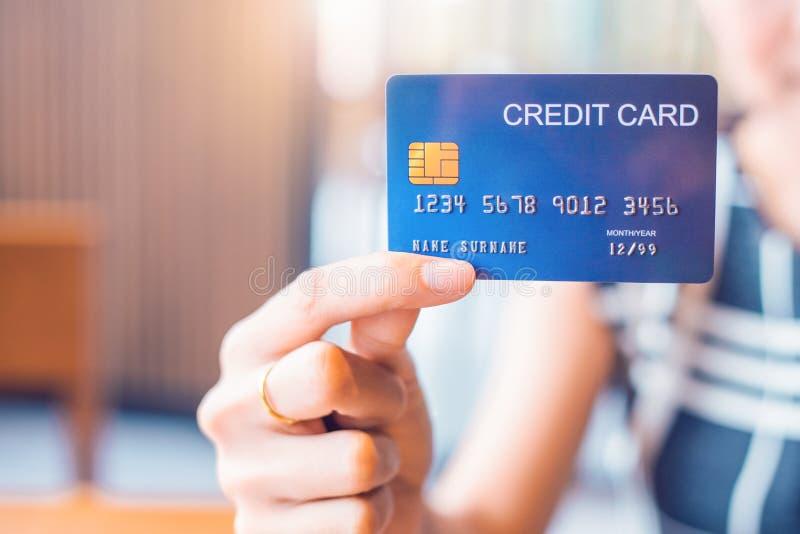 Handen f?r aff?rskvinnan rymmer en bl? kreditkort royaltyfri bild