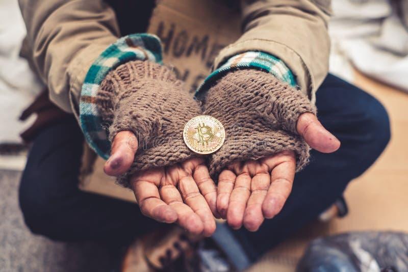 Handen gömma i handflatan hemlöns som är smutsig med, mottar donation en guld- bitcoin royaltyfria bilder