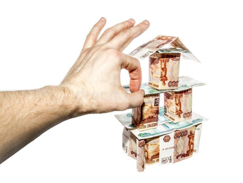 Handen gör en klick på hus av sedlar fotografering för bildbyråer