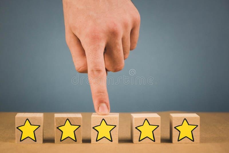 handen gör ett val och väljer en av stjärnorna, på en blå bakgrund arkivbild