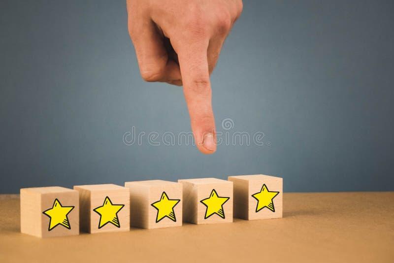 handen g?r ett val och v?ljer en av stj?rnorna, p? en bl? bakgrund royaltyfria foton