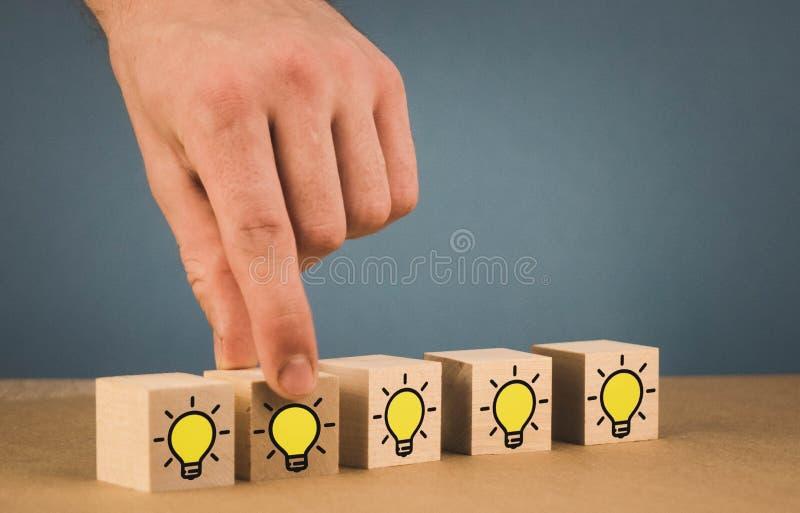 handen g?r ett val och v?ljer en brinnande ljus kula, ett symbol av en ny id? royaltyfria bilder