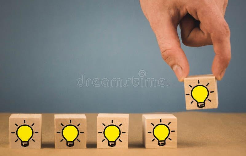 handen g?r ett val och v?ljer en brinnande ljus kula, ett symbol av en ny id? arkivbilder