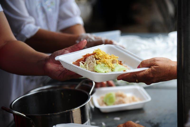 Handen ger mat till händer av en tiggare arkivfoto