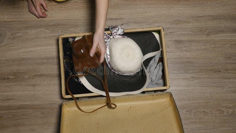 Handen gezet paspoort in koffer Kaart en paspoort op kleren Seizoen van vakantie De vrouw wordt klaar voor vlucht stock afbeelding