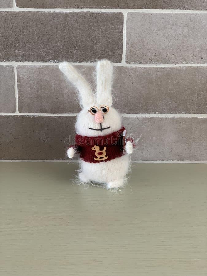 Handen - gjorde den gulliga klyftiga stack den kaninleksaken eller haren i röd tröja med hästen och boken på anseende för bakgrun arkivfoto