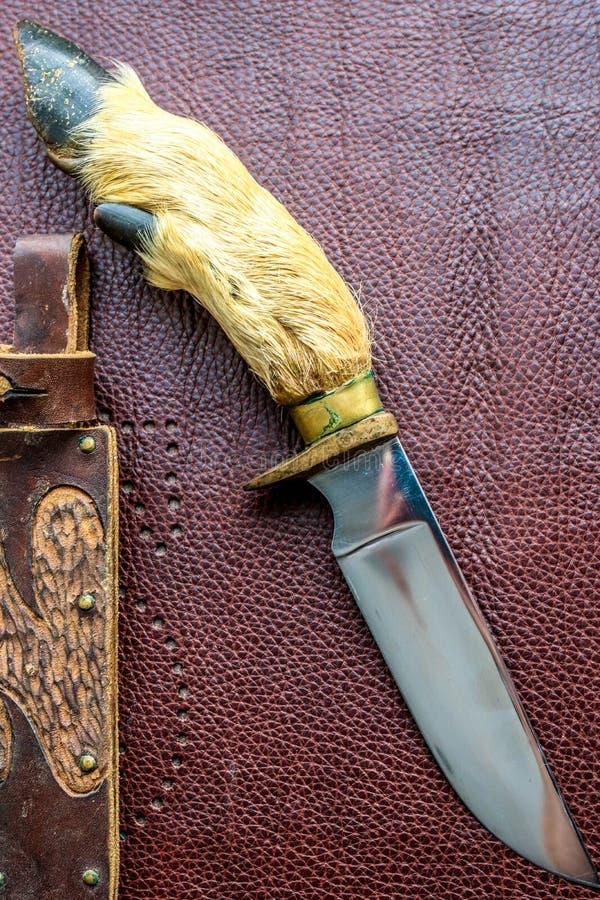 Handen - gjorde den jaga kniven på den bruna bakgrunden royaltyfri bild