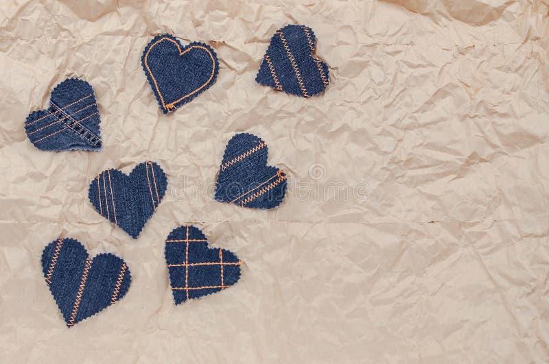 Handen - gjorde jeanshjärtor på en skrynklig hantverkpappersbakgrund Lägga framlänges, den bästa sikten, minsta stil, kopieringsu royaltyfri bild