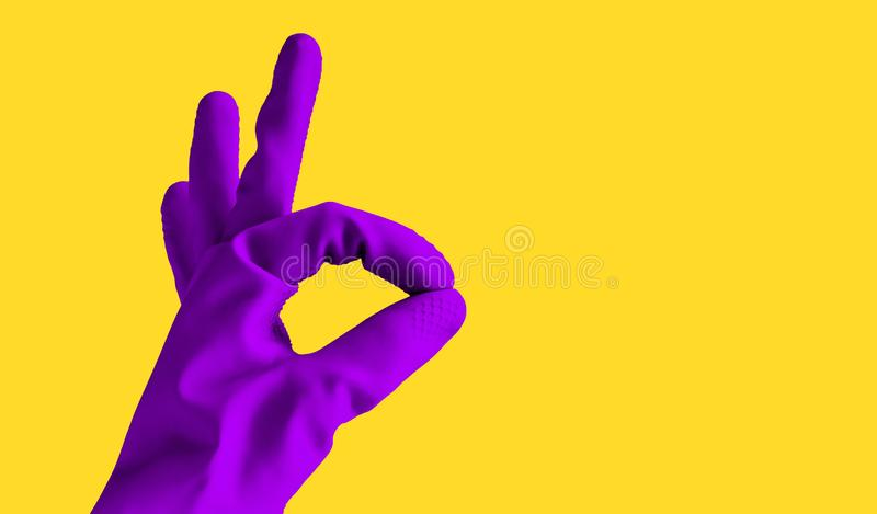 Handen i den violetta handsken för gummi visar det ok tecknet, isolerat objekt på gul bakgrund för design med kopieringsutrymme s royaltyfri foto