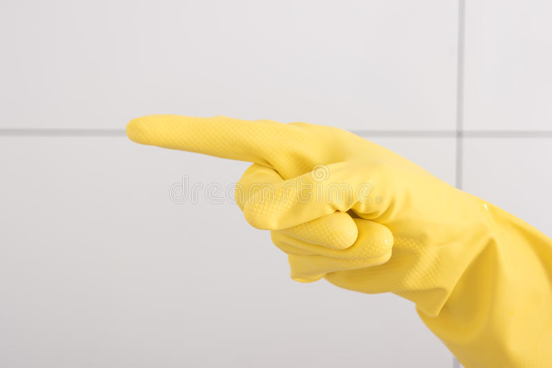 Handen i gul rubber handske visar ett pekfinger royaltyfria foton