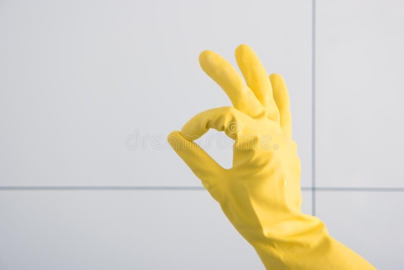 Handen i gul rubber handske visar reko royaltyfri foto