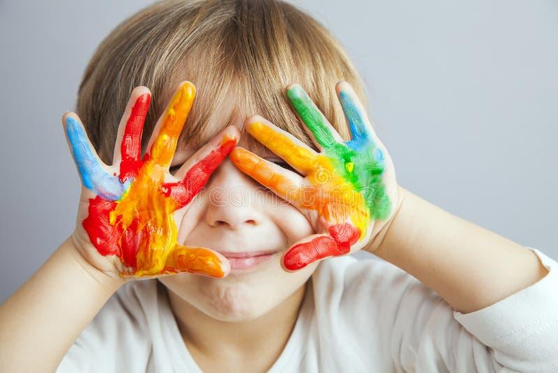 Handen in kleurrijke verven worden geschilderd die royalty-vrije stock afbeeldingen