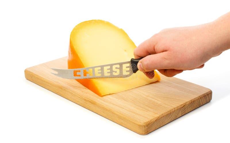 Handen klipper med kniven osten på en skärbräda fotografering för bildbyråer