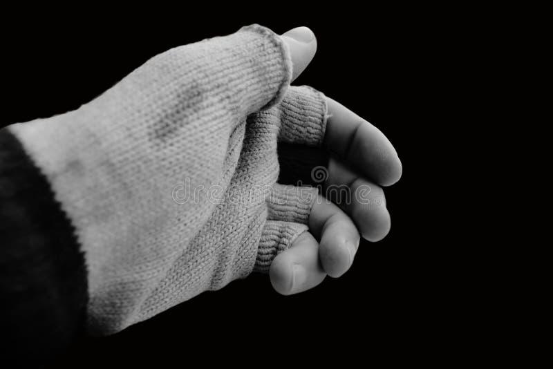 Handen med den gamla handsken, som saknar fingret, överträffar på en svart bakgrund och i svartvitt arkivbild