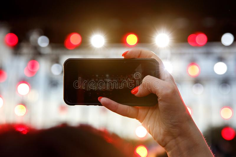 Handen med en smartphone antecknar festival för levande musik, bor konserten, lycklig ungdom arkivbild
