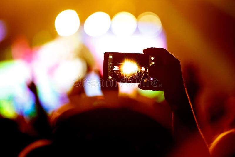 Handen med en smartphone antecknar festivalen för levande musik som tar fotoet av konsertetappen arkivbild