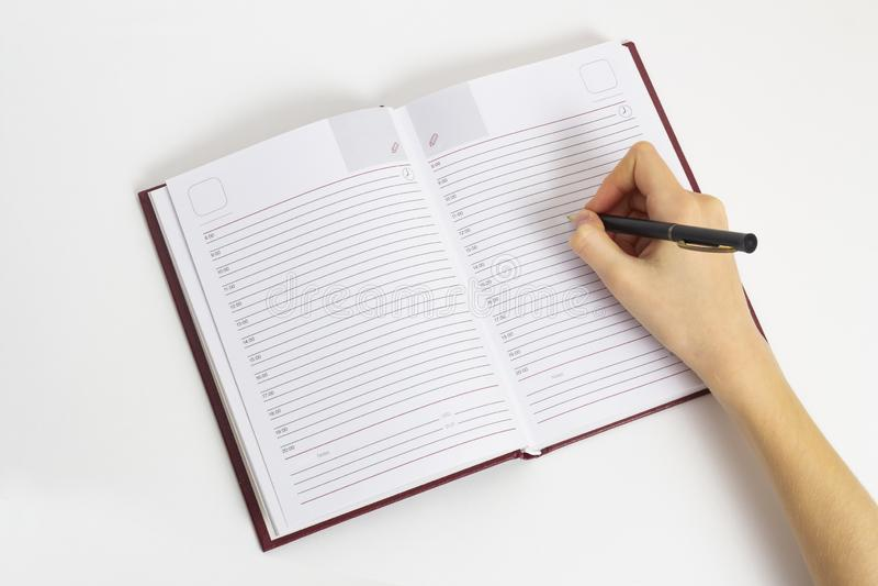 Handen med pennan är klar att skriva i en öppen anteckningsbok royaltyfria bilder