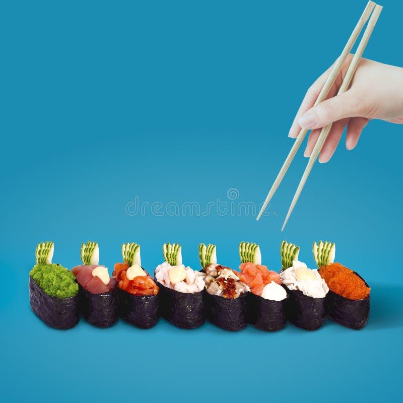 Handen med pinnar väljer sushi på en blå bakgrund arkivbild